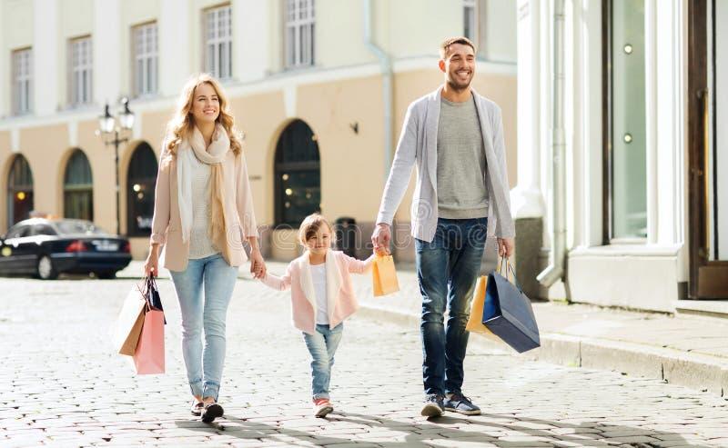 Szczęśliwa rodzina z dzieckiem i torba na zakupy w mieście zdjęcia royalty free