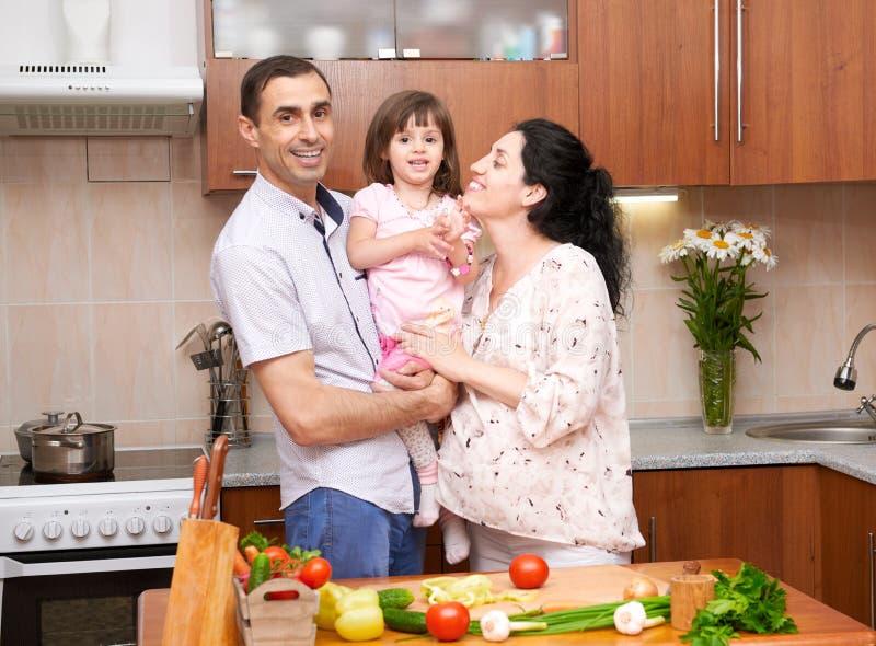 Szczęśliwa rodzina z dzieckiem w domowym kuchennym wnętrzu z świeżymi owoc i warzywo, kobieta w ciąży, zdrowy karmowy pojęcie obraz royalty free