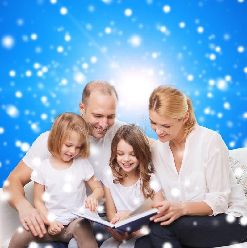 Szczęśliwa rodzina z książką w domu obrazy stock
