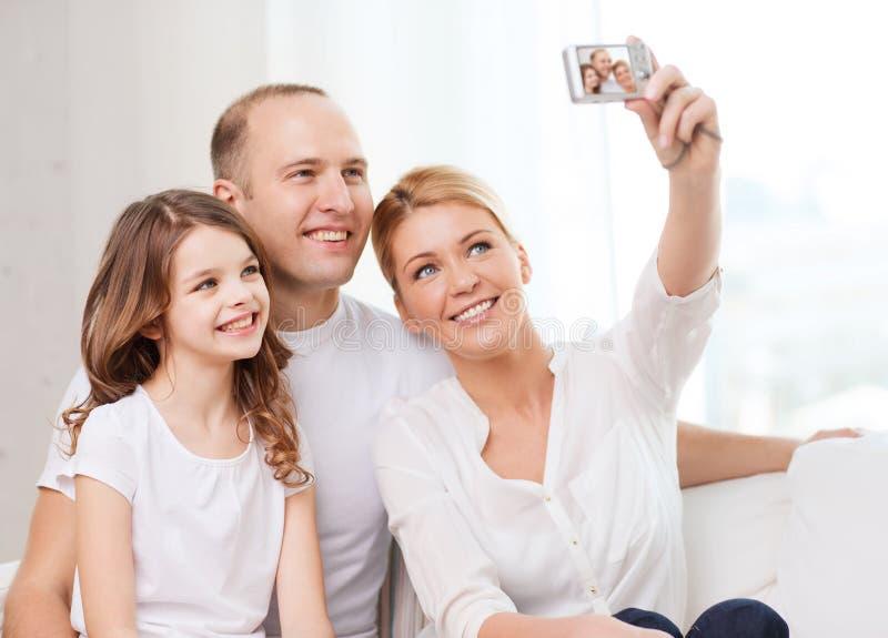 Szczęśliwa rodzina z małą dziewczynką robi jaźń portretowi zdjęcia stock