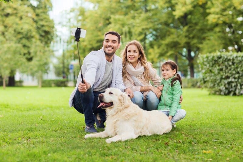 Szczęśliwa rodzina z psem bierze selfie smartphone zdjęcia stock
