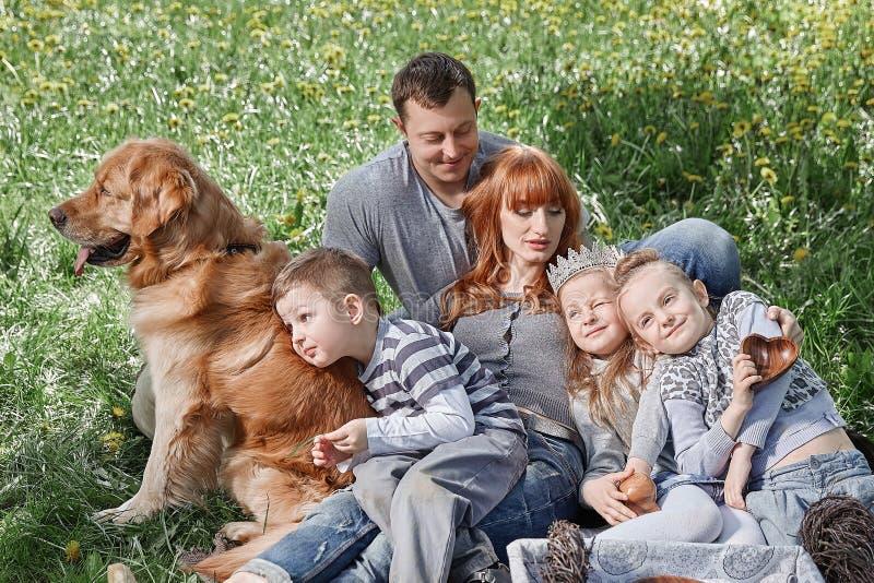 Szcz??liwa rodzina z trzy dzieciakami siedzi na trawie w Pogodnym parku fotografia stock
