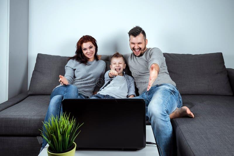 Szczęśliwa rodzina z uśmiechami oglądającymi coś na laptopie Koncepcja wspólnych pastwisk, wakacji, wspólnego wypoczynku, rodziny zdjęcia stock