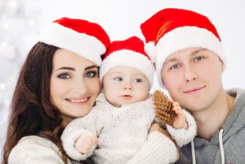 Szczęśliwa rodzina z uroczym dzieciakiem ma zabawę przy choinką zdjęcie royalty free