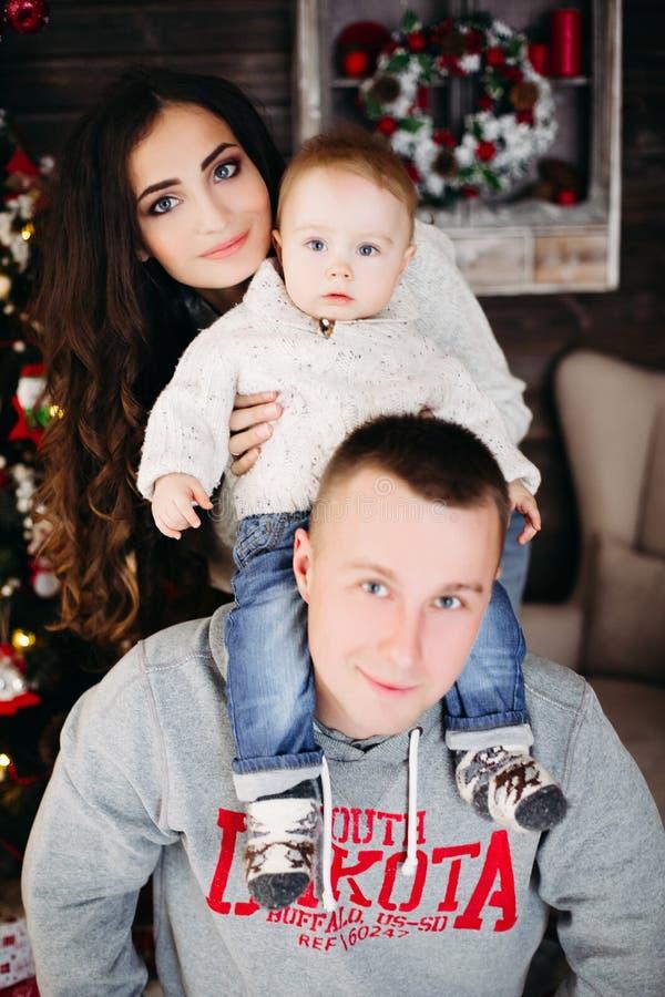 Szczęśliwa rodzina z uroczym dzieciakiem ma zabawę przy choinką zdjęcie stock