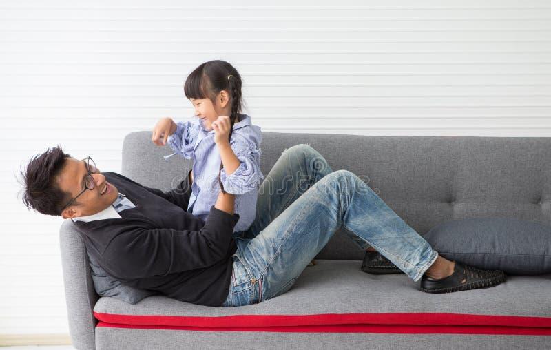 szczęśliwa rodzinna Śliczna małej dziewczynki córka, ojciec i jesteśmy ściskający i bawić się na kanapie w żywym pokoju w domu wy zdjęcia royalty free