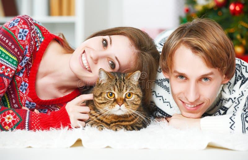 Szczęśliwa rodzinna para i kot w bożych narodzeniach w domu obrazy royalty free