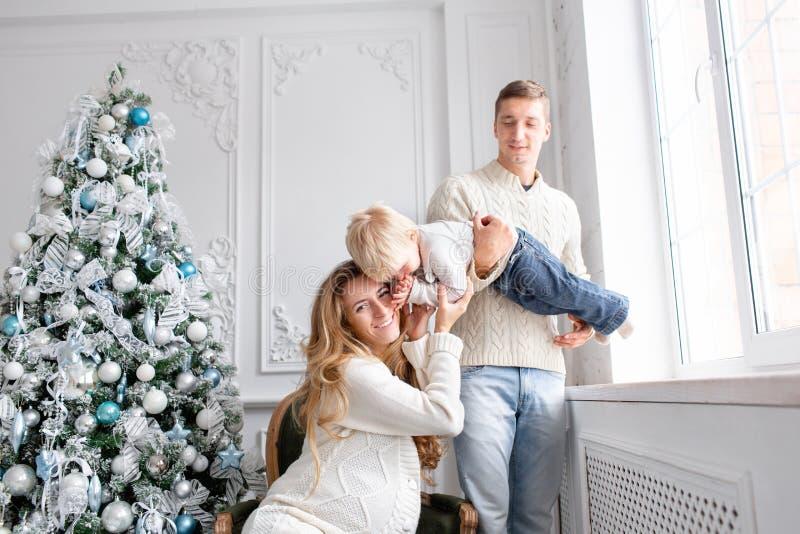 szczęśliwa rodzinna zabawa mieć domowego Poranek bożonarodzeniowy w jaskrawym żywym pokoju Potomstwo rodzice z małym synem ojciec fotografia royalty free