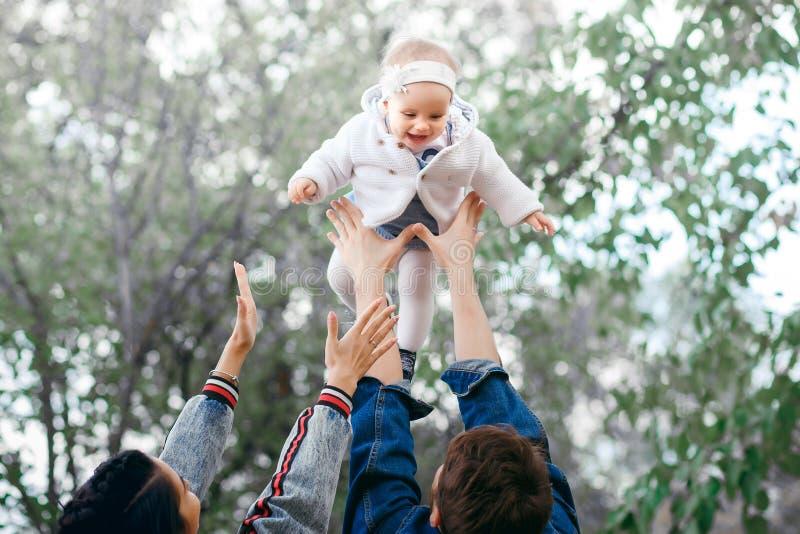 Szczęśliwa rodziny aktywność outdoors, ojciec podnosi dziecka w górę, śmiający się i bawić się, ojców przedstawienia matkują dlac fotografia stock