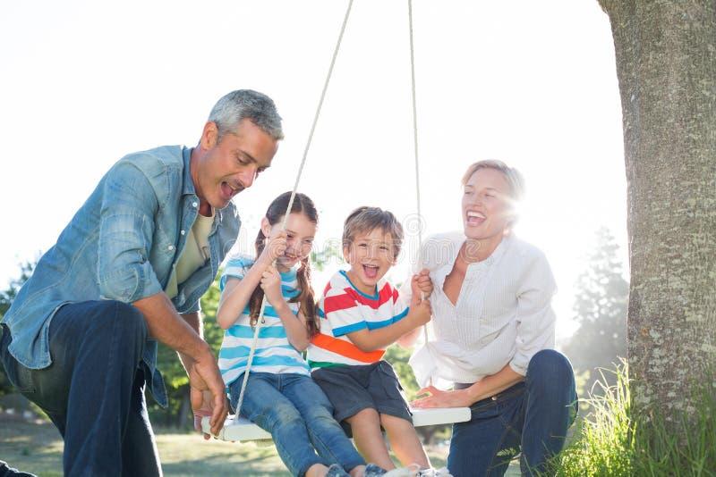 Szczęśliwa rodziny huśtawka obrazy stock