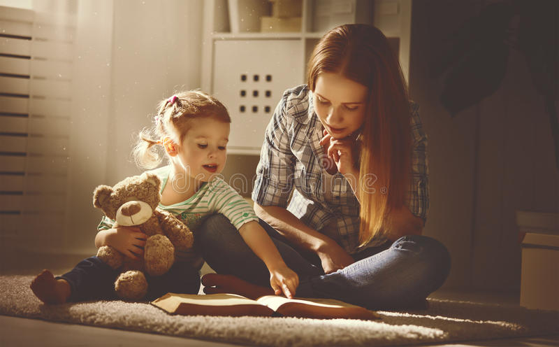 Szczęśliwa rodziny matka, córka i czytamy książkę w wieczór fotografia stock