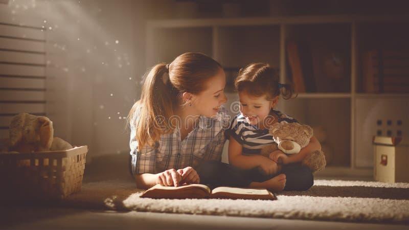 Szczęśliwa rodziny matka, córka i czytamy książkę w wieczór obraz royalty free