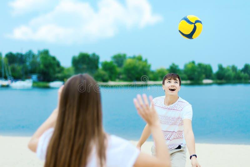 Szczęśliwa romantyczna para bawić się z piłki nożnej piłką w lecie zdjęcia stock