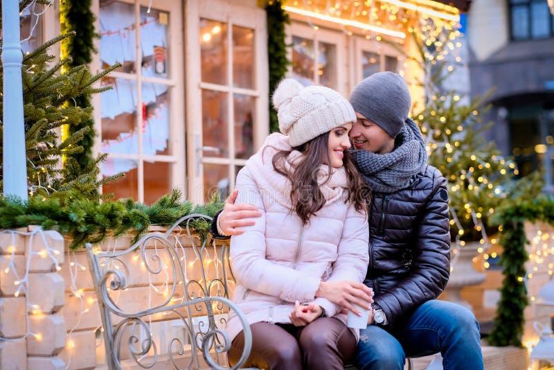 Szczęśliwa romantyczna para jest ubranym ciepłych ubrania, cieszy się wydający czas wpólnie na dacie, ściska podczas gdy siedzący fotografia stock