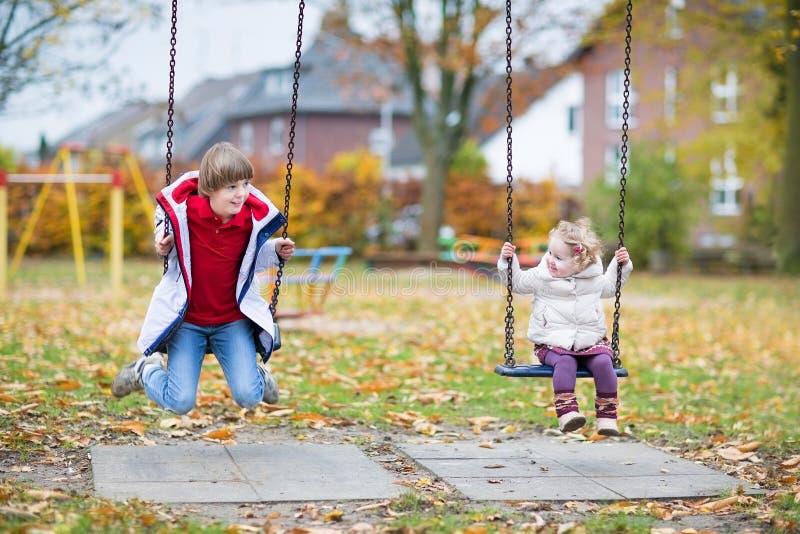 Szczęśliwa roześmiana chłopiec i dziecka siostra bawić się na huśtawce fotografia royalty free