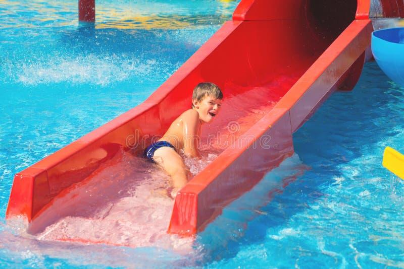 Szczęśliwa rozochocona caucasian chłopiec na wodnym obruszeniu przy aqua parkiem fotografia stock