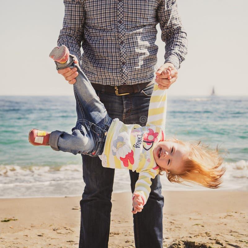 Szczęśliwa rozochocona kochająca rodzina, ojciec i mała córka bawić się na plaży, potomstwo ojciec holging jego dzieciaka do góry zdjęcie stock