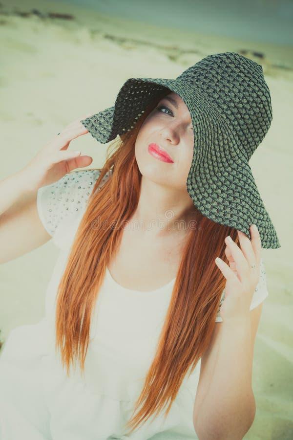 Szczęśliwa rudzielec kobieta jest ubranym dużego czarnego słońce kapelusz obrazy royalty free