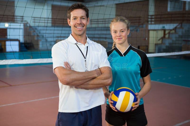 Szczęśliwa samiec trenera i siatkówka gracza pozycja w sądzie zdjęcia stock