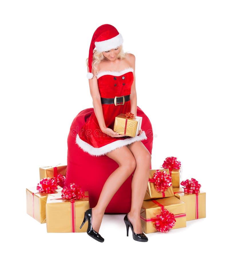 Szczęśliwa Santa kobieta z nikłym nogi siedzeniem na bożych narodzeniach grabije z obrazy royalty free
