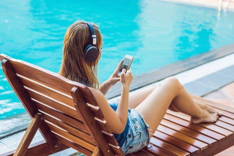 Szczęśliwa smartphone kobieta relaksuje blisko pływackiego basenu słuchania z earbuds lać się muzykę Piękna dziewczyna używa ona obrazy stock