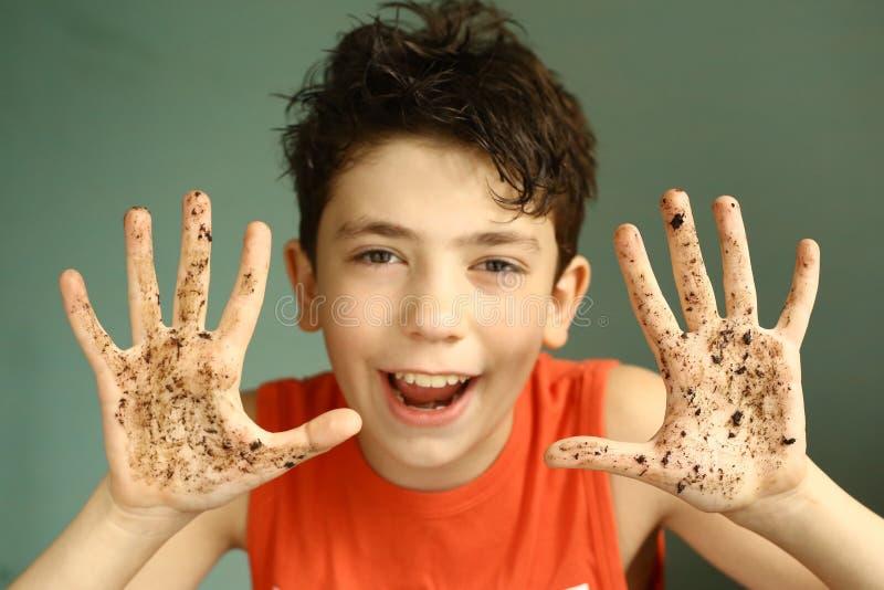Szczęśliwa sowizdrzalska nastolatek chłopiec z brudnymi rękami zdjęcie royalty free