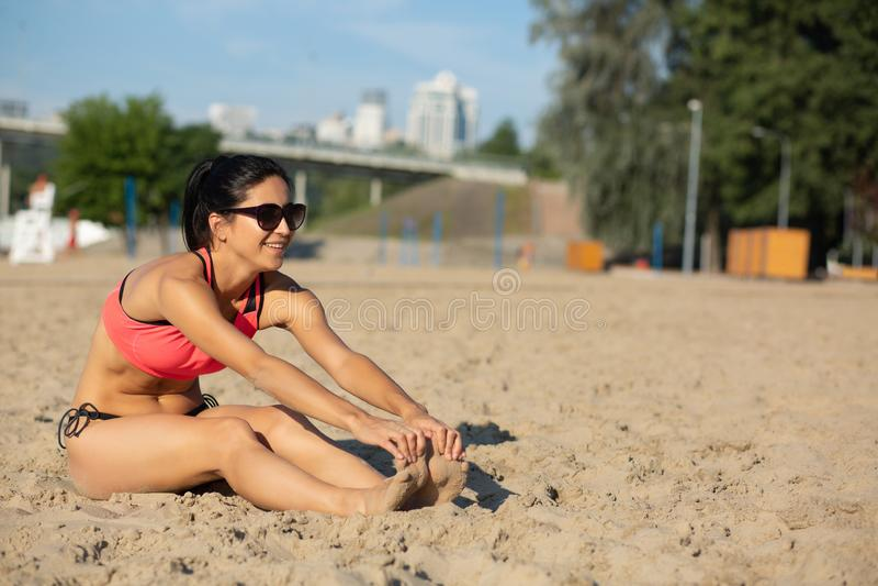 Szczęśliwa sprawności fizycznej dziewczyna w okularach przeciwsłonecznych rozciąga przy plażą w ranku Opróżnia przestrzeń zdjęcia royalty free