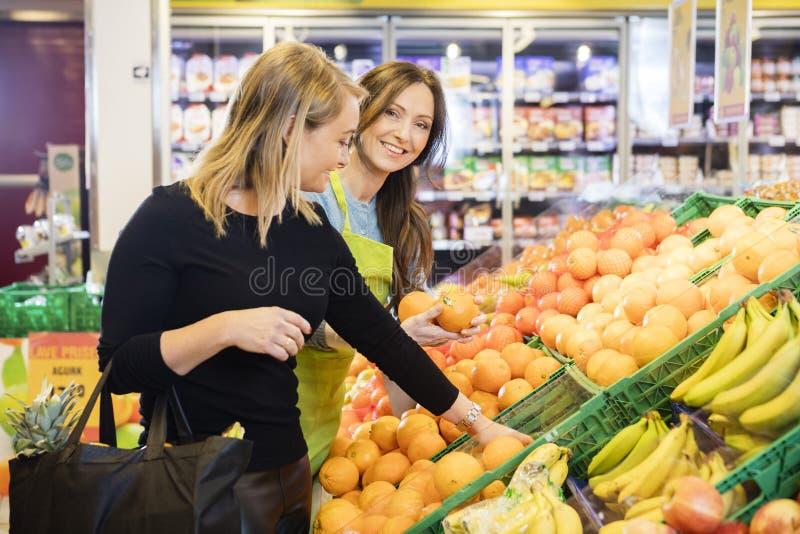 Szczęśliwa sprzedawczyni pozycja Żeńskim klientem Wybiera pomarańcze obraz royalty free
