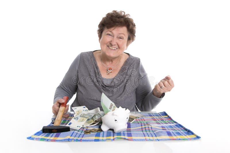 Szczęśliwa stara kobieta - bogata osoba po niszczącego prosiątko banka obraz stock