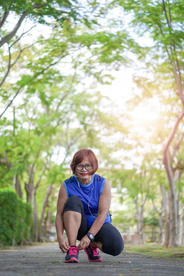 Szczęśliwa starsza azjatykcia kobieta jogging przez parka wiąże obuwiane koronki zdjęcia stock