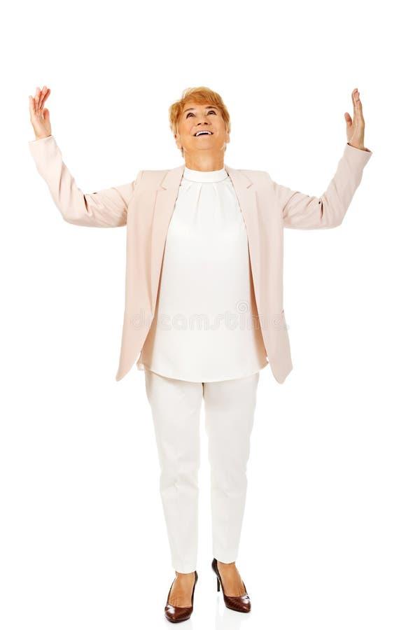 Szczęśliwa starsza biznesowej kobiety próba łapać coś obraz royalty free