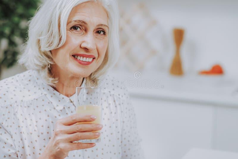 Szczęśliwa starsza dama cieszy się świeżego napój salowego obrazy royalty free