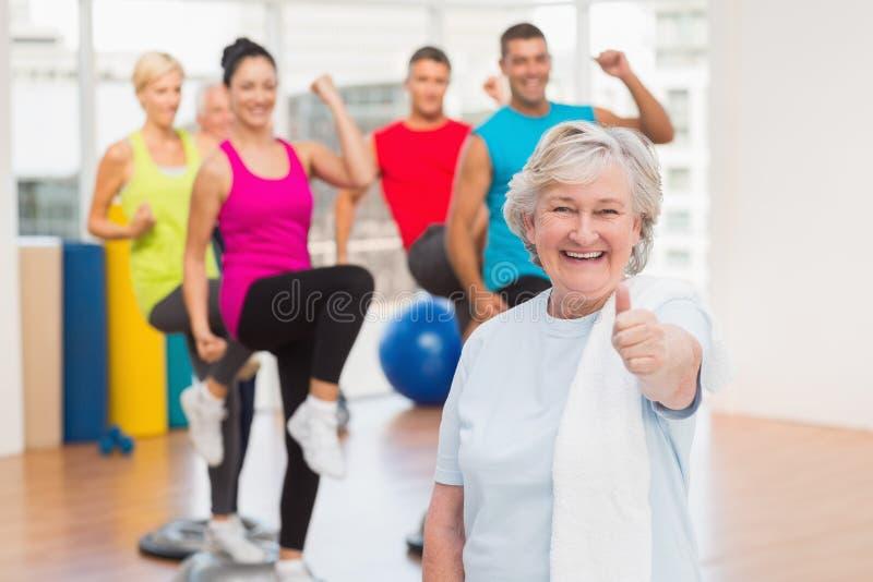 Szczęśliwa starsza kobieta gestykuluje aprobaty przy gym obraz stock