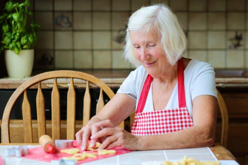 Szczęśliwa starsza kobieta robi ciastkom przy kuchnią zdjęcie stock