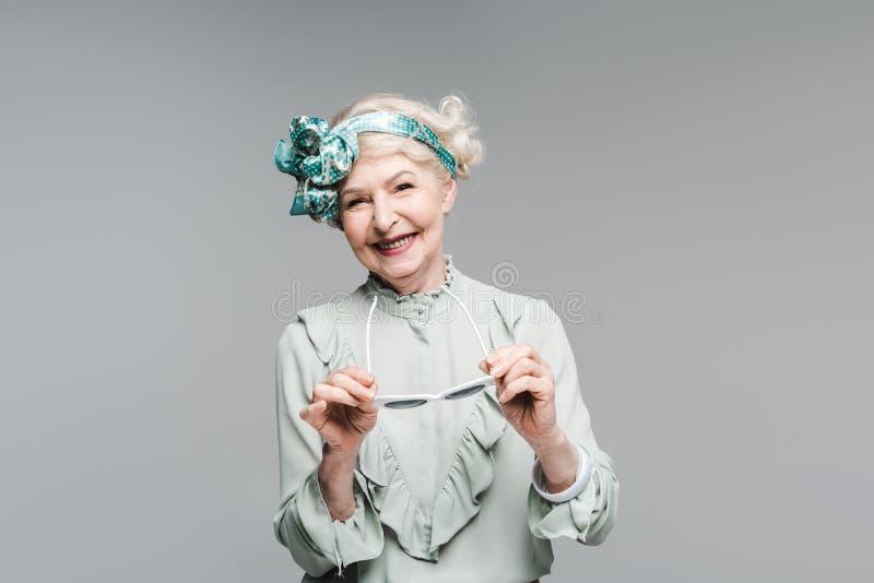 szczęśliwa starsza kobieta w eleganckim roczniku odzieżowym i okularach przeciwsłonecznych zdjęcie royalty free