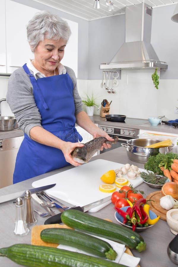 Szczęśliwa starsza kobieta w kuchennego narządzania świeżej ryba obrazy royalty free
