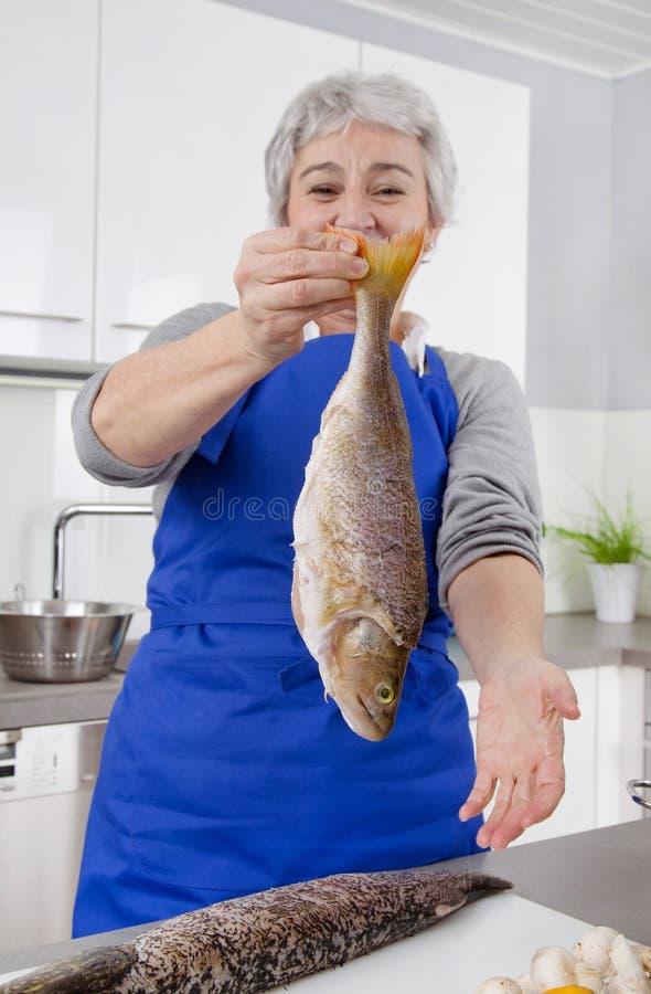 Szczęśliwa starsza kobieta w kuchennego narządzania świeżej ryba obraz royalty free