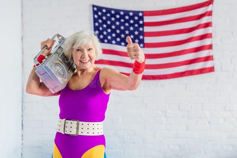 szczęśliwa starsza kobieta w sportswear mienia taśmy seansie i pisaku fotografia stock