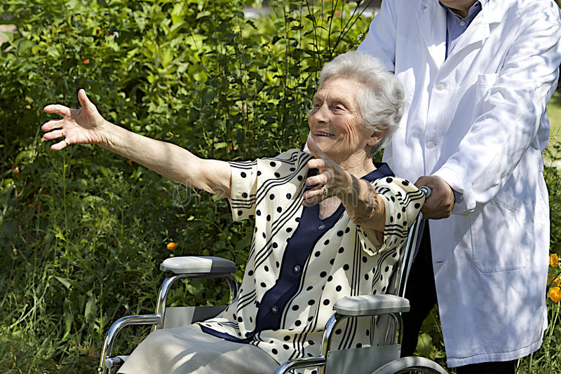Szczęśliwa starsza kobieta w wózku inwalidzkim z otwartymi rękami fotografia royalty free
