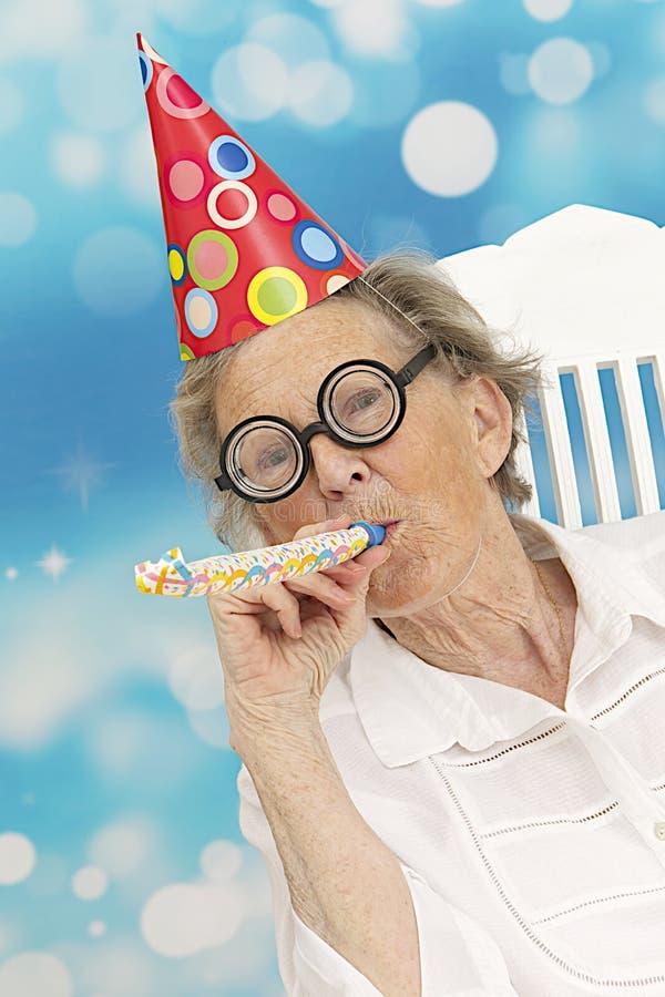 Szczęśliwa starsza kobieta z śmiesznymi szkłami partyjny kapelusz i hałasu producent zdjęcia royalty free