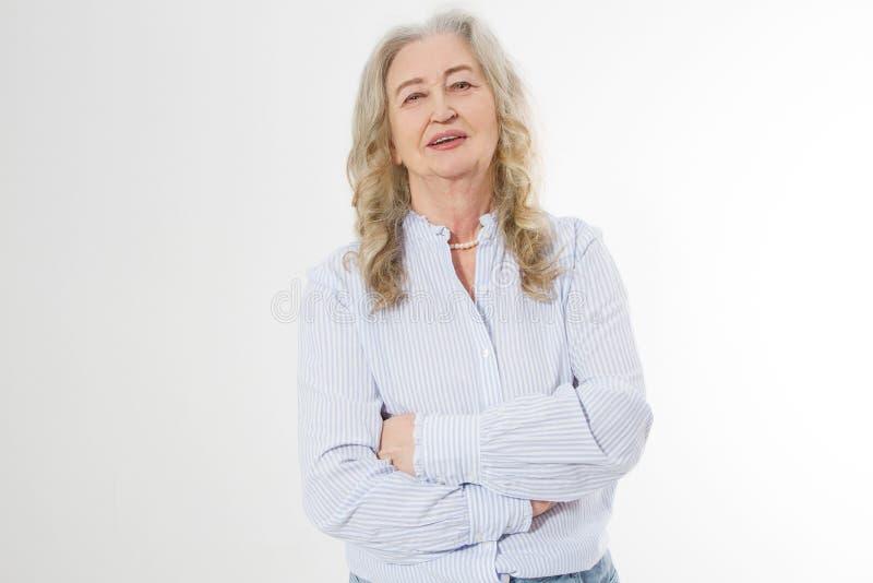 Szczęśliwa starsza kobieta z krzyżować rękami odizolowywać na białym tle Pozytywny starszy seniora życia utrzymanie i europejski  zdjęcia stock
