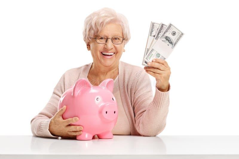Szczęśliwa starsza kobieta z piggybank i pieniędzy plikami zdjęcie royalty free
