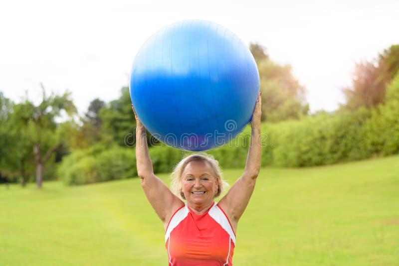 Szczęśliwa starsza kobieta z stabilności piłki koszt stały zdjęcie stock