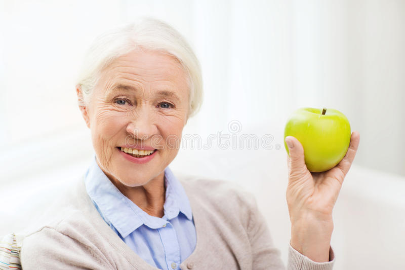Szczęśliwa starsza kobieta z zielonym jabłkiem w domu zdjęcie royalty free