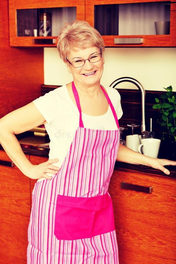 Szczęśliwa starsza kobiety pozycja w kuchni fotografia royalty free