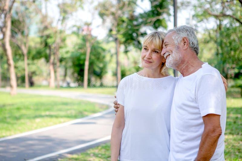 Szczęśliwa starsza kochająca para relaksuje przy parkowy obejmować wpólnie w ranku czasie starzy ludzie ściska i cieszy się wydaj obrazy stock