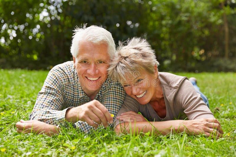 Szczęśliwa starsza para kłaść w trawie obrazy stock