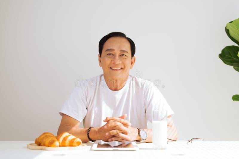 Szczęśliwa starsza para ma croissant śniadanie i napój w domu obrazy royalty free