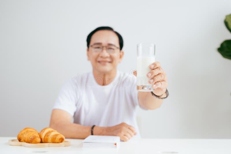 Szczęśliwa starsza para ma croissant śniadanie i pije mleko w domu fotografia stock