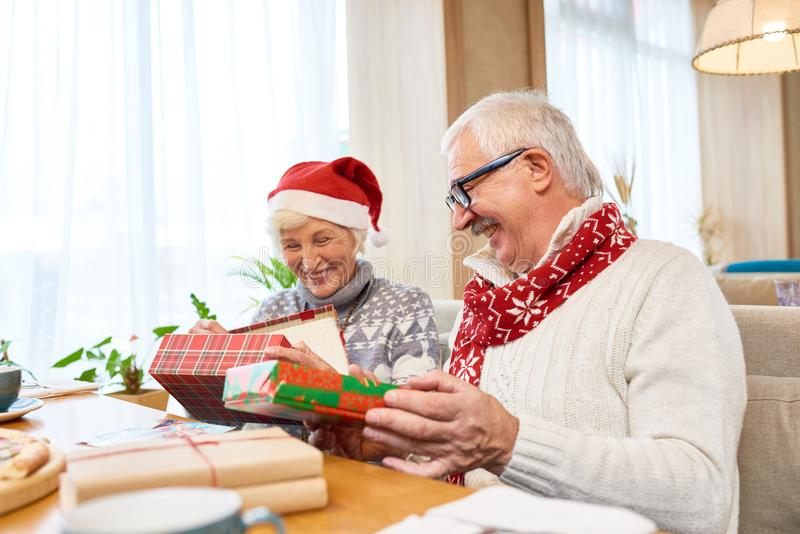 Szczęśliwa Starsza para Otwiera Bożenarodzeniowe teraźniejszość zdjęcia royalty free